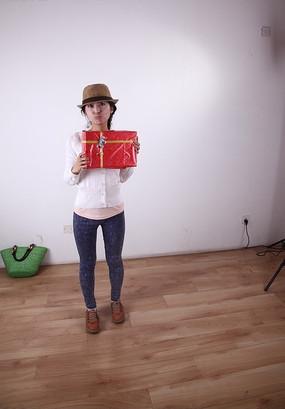 双手举着红色礼盒的女人