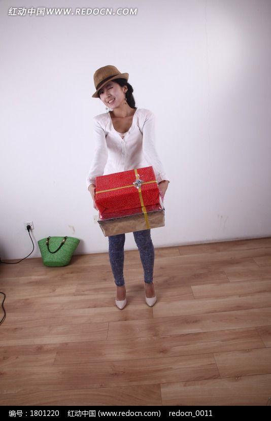 戴着帽子抱着礼盒的女人图片