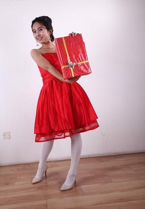 穿红色礼服双手拿着红色礼盒的女人