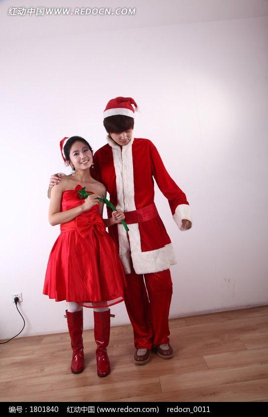 手拿红玫瑰看着地面的圣诞情侣