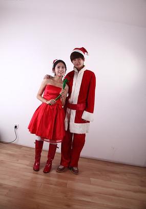 手拿红玫瑰看着前方的圣诞情侣