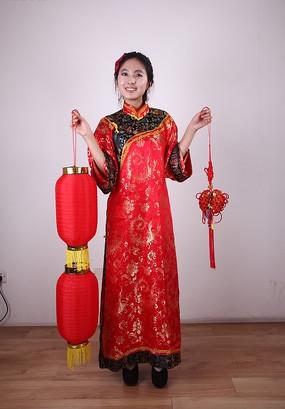 右手提着灯笼左手提着中国结的唐装美女