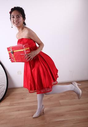 双手抱着红色礼盒左腿后踢的女孩