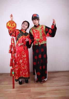 新年人物摄影 手拎爆竹与红辣椒装饰的古装新郎新娘