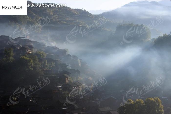山间阳光穿过迷雾的苗家寨