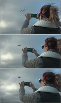 美女拿手机拍摄飞机视频