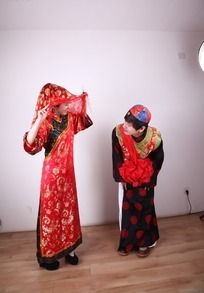 新郎蹲身偷看红盖头下新娘
