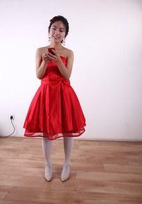 穿红色礼服使用手机的女人