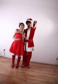 圣诞装的男人搂着拿着康乃馨的女人