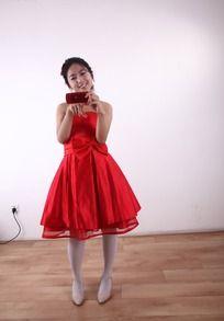微笑着看着手机的红色礼服女人