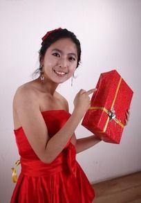 右手指着左手拿着的礼盒的女人