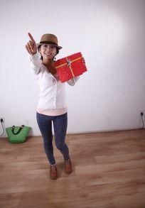左手拿着红色礼盒右手前指的女人