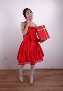 拿着红色礼盒闭着眼睛打电话的美女