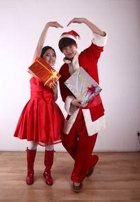 拿着礼盒摆心形姿势的圣诞服饰恋人模特