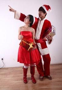 拿着礼盒遥望侧方的圣诞节情侣