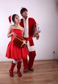 穿圣诞装拿着礼盒的一对男女