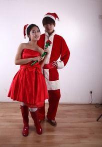 圣诞装的男人和穿红礼服拿着花的女人