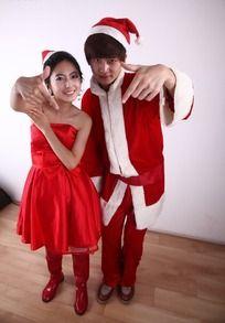 一起摆pose穿着圣诞服装和红色礼服的情侣