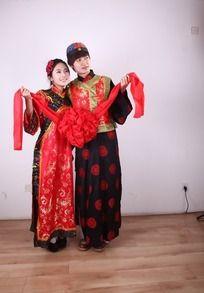 身穿古装拿着大红花恩爱的新郎新娘