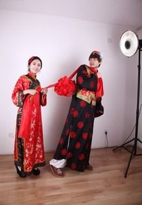 新郎手持大红花转头看新娘的图片