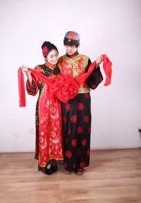 新郎新娘深情注视大红花的图片