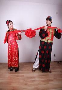 红绸两头穿古代结婚礼服的新郎新娘