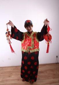手拿红色中国结侧头微笑的古装男人
