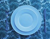 花图案背景上的白色碟子和西餐餐具刀叉