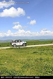 停靠在蓝天白云下的草地上的越野观光车