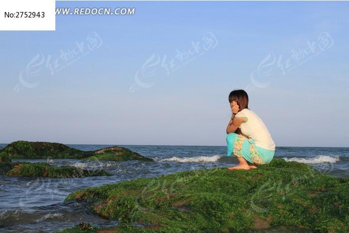 站在海边石头上沉思的女生图片