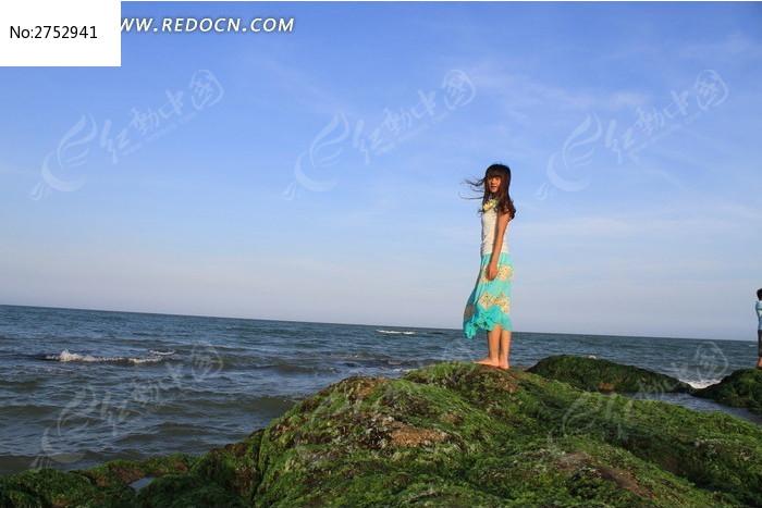 站在海边石头上的女生