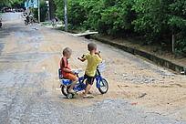 骑自行车玩耍的两个小孩