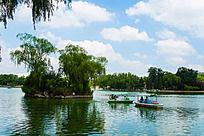 蓝天白云下龙潭湖上的小岛和泛舟小船