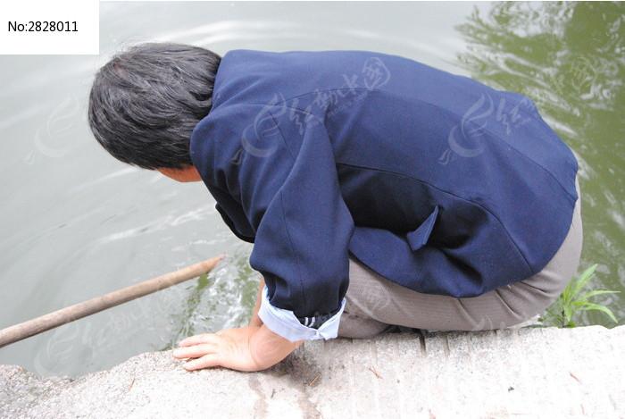 在河边辛勤劳动的老人