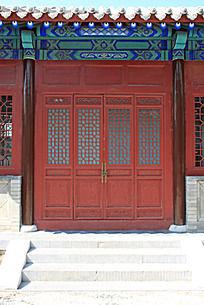 园林里古建筑上的红色中式雕刻彩绘门窗和彩绘图案图片