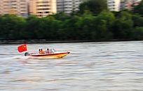 插中国国旗的赛艇快速驶过