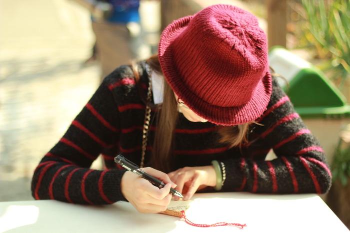 低头写字 学习 思考 戴帽子的女子