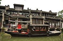 河边古建筑旁停靠的木船
