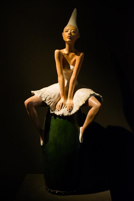 身着芭蕾舞裙叉腿坐在圆桶上的热辣美女塑像