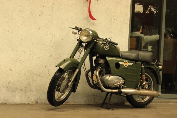 广州红砖厂红蜘蛛特色店门口的复古军绿色摩托车装饰品