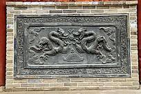 青砖墙面上雕刻的龙纹图案