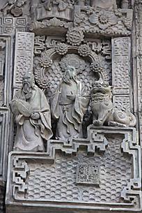 石头狮子边的两个人物雕塑