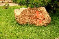 绿色草地上雕刻寿字的大石头