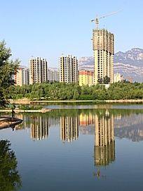 建设中的高楼对称的湖中倒影