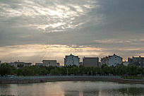 夕阳的光线透过云层照在小区楼房及水面
