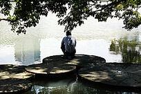 有人蹲在圆石盘上看对岸倒影