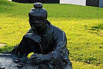绿色草地上的下棋的男子雕像