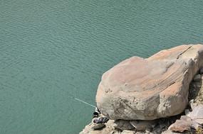 河边巨石后的钓鱼人