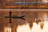 黄昏时段渔民在江面上捕鱼