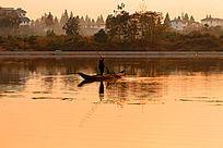 金色水面上一艘打渔船